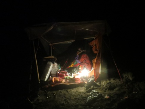 A woman with a small tent half way down the crater.