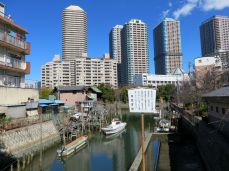 Little river inlet with more high rises and fishing boats.