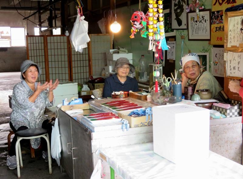 Women chatting in fish market Aomori